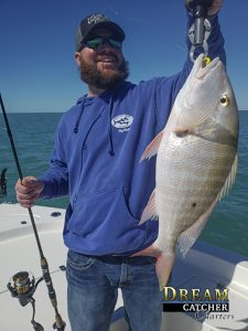 Mutton Snapper being held up by an angler with a boga grip that went fishing with Dream Catcher Charters in Key West.