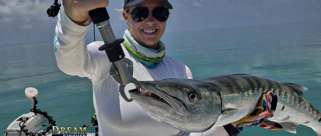 Lady angler holds up a nice barracuda