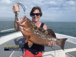 Red Grouper being held up by lady angler fisherman